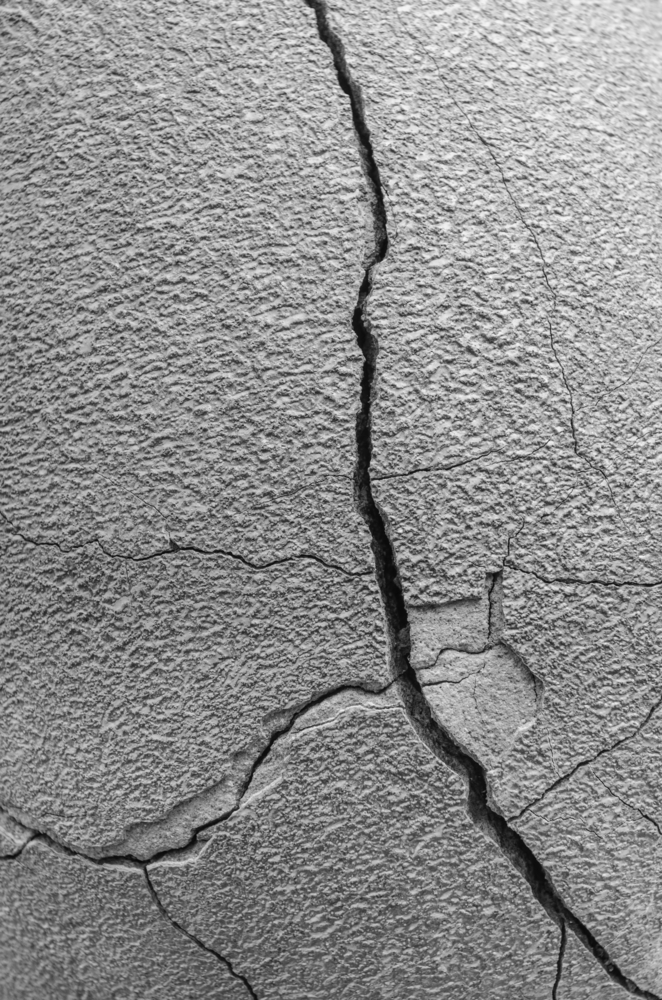 Garden abstract in black and white Closeup of long crack, with tributaries, in the side of a large planter, for concepts of time, pressure, susceptibility, or imperfection